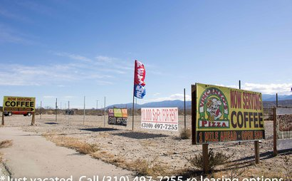 HWY 138 ADJACENT - LAND + SHOPPING CENTER (UP TO GRADED LAND + 70 MARKED PAVED PARKING SPACES); Storage/Basecamp/Filming/storage. Tons parking/fenced area.